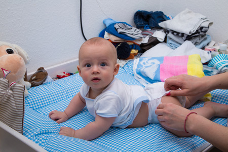 nursling: Cheerful newborn playing on the diaper table.
