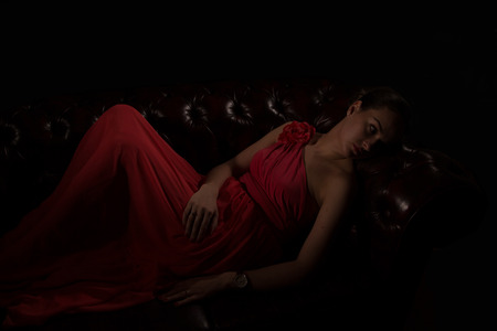 bodyparts: Beautiful woman in red evening dress in dark environment Stock Photo