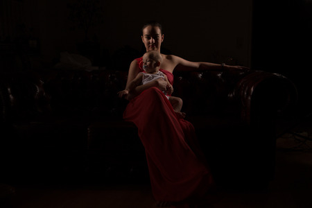 red evening: Beautiful woman with her child in red evening dress in dark environment