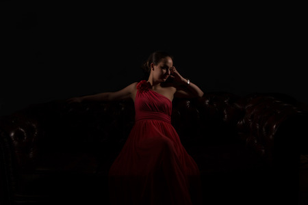 red evening: Beautiful woman in red evening dress in dark environment Stock Photo