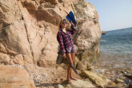 harpoon: Girl with harpoon in flannel shirt on the rocky beach.