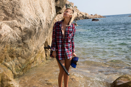 flannel: Girl with harpoon in flannel shirt on the rocky beach.
