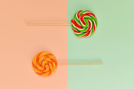 A pair of candies on a wooden stick on a geometric background. Postcard. Birthday Sweet Caramel. This is an empty place. Top View Flatlay Layout