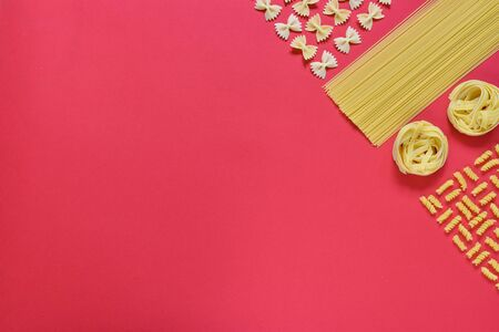 Various pasta on a red background in the upper right corner. Empty place for text, quote, sayings or logo on a mint background.