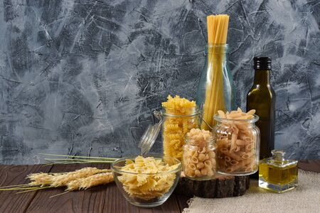 Various dry pasta with ingredients for cooking: flour, butter, egg. various types of pasta, pasta, fusilli, conciglio, rigatoni, farfalle, penne. Dinner. Healthy food. Empty place for text, quote, sayings or logo on a mint background. Copy space.