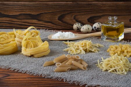Various dry pasta with ingredients for cooking: flour, butter, egg. various types of pasta, pasta, fusilli, conciglio, rigatoni farfalle penne