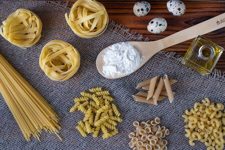 Various dry pasta with ingredients for cooking: flour, butter, egg. various types of pasta, pasta, fusilli, conciglio, rigatoni, farfalle, penne. Dinner. Healthy food Top View Flatlay Layout