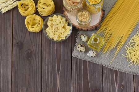 Various pasta on a wooden background at the top. Dinner. Healthy food. Empty place for text, quote, sayings or logo on a mint background. Top View Flatlay Layout