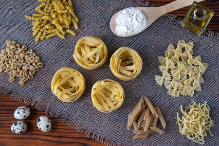 Various dry pasta with ingredients for cooking: flour, butter, egg. various types of pasta, pasta, fusilli, conciglio, rigatoni, farfalle, penne. Dinner. Healthy food. Flalay. Top view.