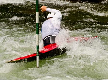 paddler: Kayak paddler around the gate Editorial
