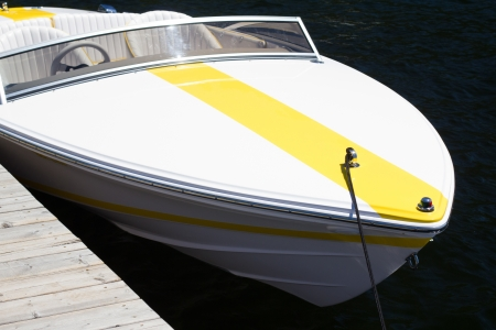 white boat with yellow stripe
