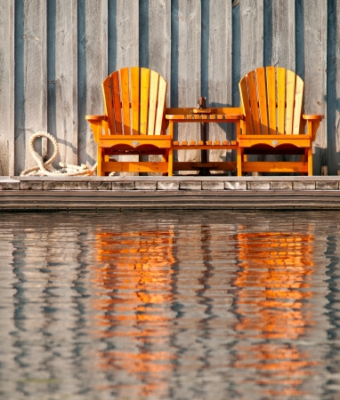 Two wooden chairs reflected in the water photo