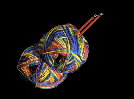 Colorful knitting yarn and two red needles Фото со стока