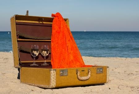 Vintage suitcase avec deux verres de vin sur la plage de sable Banque d'images
