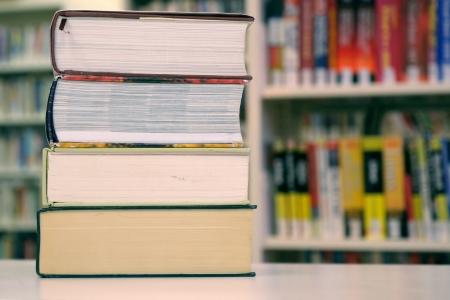 Pile de grands livres contre une �tag�re de biblioth�que