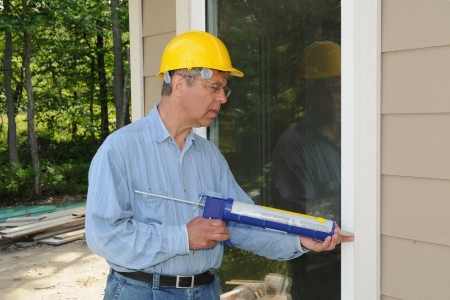 windows: Construction worker with a caulking gun Stock Photo