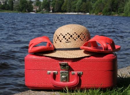 Valise rouge, chapeau de paille et des sandales