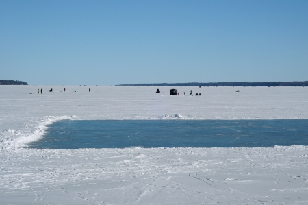 barrie: Frozen lake with a skating rink and fishing huts