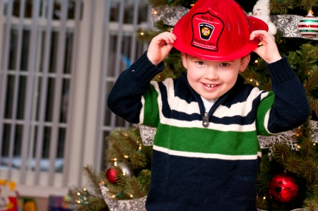 Small boy with a toy fireman hat Stock Photo
