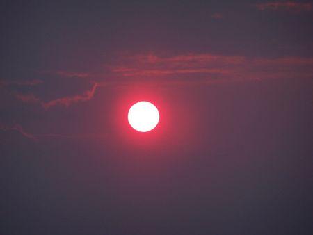 White sun on purple sky. Sunset before storm. photo