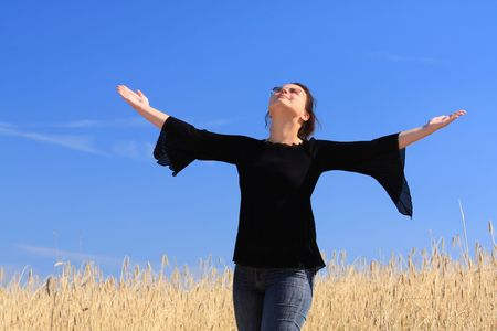 Happy woman on the wheat field. Thanks to heavens/