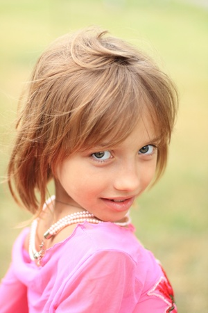 Portrait of the beautiful litle girl in pink, wearing pearl beads photo