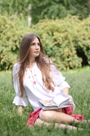 Portrait of the beautiful girl in ukrainian dress. Sitting on the grass. photo