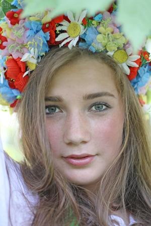 Portrait of the beautiful girl wearing traditional ukrainian crown of flowers photo