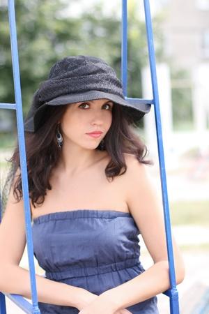 Portrait of beautiful  brunette woman in black hat sitting on swing photo