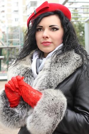 Portret van de elegante jonge vrouw, gekleed in rode hoed en rode handschoenen