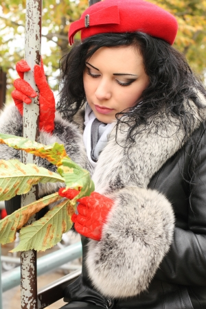 Portrait of the attractive woman in coat with fur holding fallen leaf Imagens