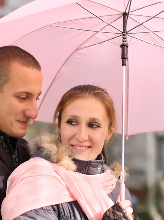 Portrait of the loving couple under pink umbrella