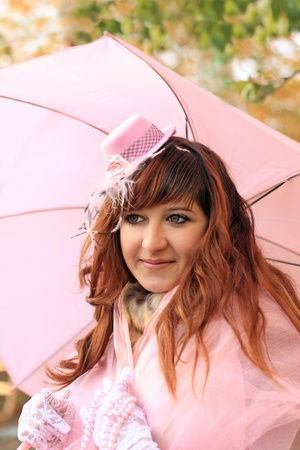 brown haired girl: Portrait of the young brown haired girl wearing pink hat with pink umbrella Stock Photo
