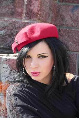 Portrait of the beautiful young brunette wearing crimson hat Stock Photo - 13840718