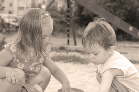 interraction: Portrait of the two little lovely kids playing in the sandbox