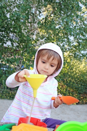 Little pretty girl while playing with funnel and sand, studying physics Stock Photo - 14553933