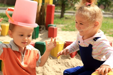 Portret van de twee grappige mooie kinderen spelen in de zandbak Stockfoto