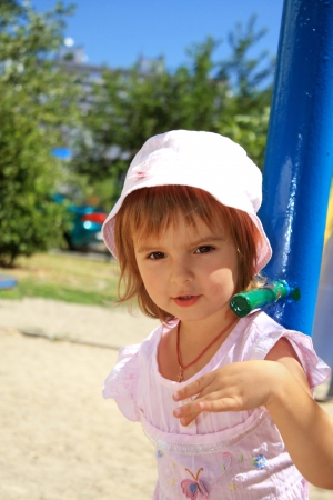 Outdoors portrait of the little lovely girl on playground photo