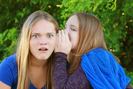 Amazement. Sharing secrets. Sisters talk Stock Photo
