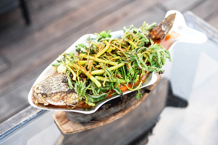 giant snakehead: Steamed tamarind flavored giant snakehead fish soup with water mimosa or sour soup. Thai food. Sour soup with fish and mixed veggies. Kang Som Pa Chon. Stock Photo