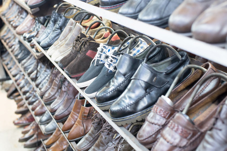 Many used shoes. Shop of second hand shoes with chair for to wear shoes.