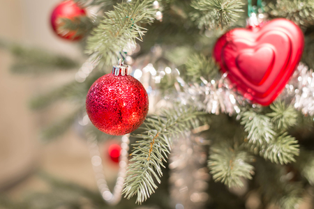 Red and silver ball hanging from a decorated Christmas tree. Stock Photo
