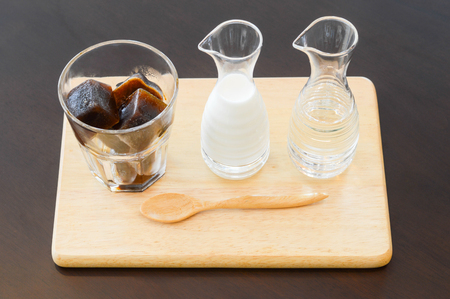 Ice coffee in ice-cube shape with steam milk and syrup on wooden. Frozen coffee cubes.
