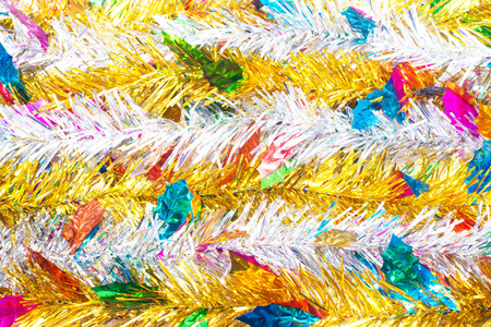 christamas: Silver tinsel and Gold tinsel with colorful leaves christmas tree background. hanging for Christmas decoration.