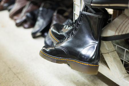second floor: Black Boots for sale in shop of second hand shoes. Stock Photo
