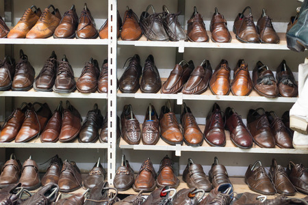 second floor: Shoes on shelf in second hand shoes shop for sale.