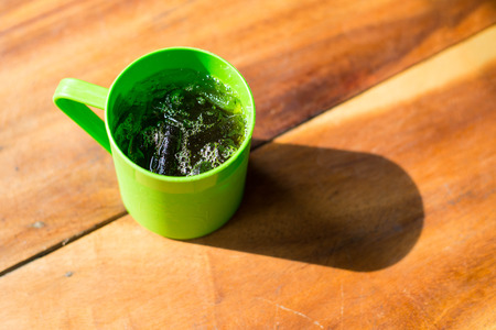 Retro styled photo of Cola in green plastic glass on wooden table.