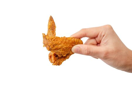 Hand holding fried chicken wing.