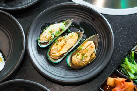 Raw mussels on black plate.