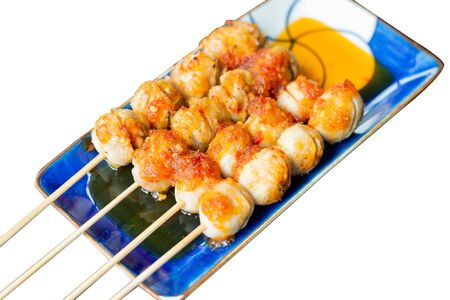 Grilled meatballs on top with sweet and sour sauce isolated on white background.